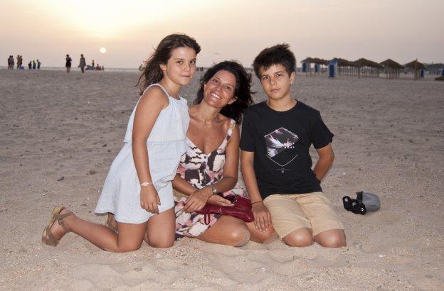 Claire Álvarez con sus hijos Pedro y Chloé en la playa, en Conil de la Frontera, al atardecer.