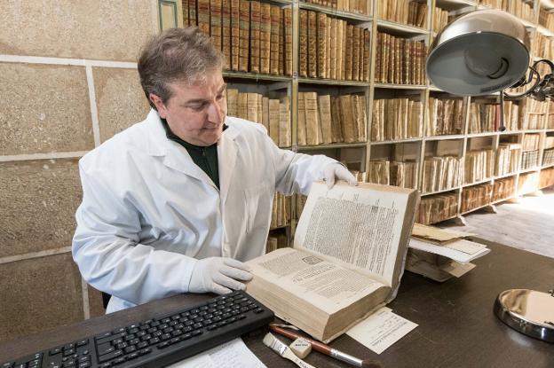 Gorka Díaz inspecciona uno de los cerca de 5.000 volúmenes de entre los siglos XVI y XVIII que se conservan en la biblioteca. :: andy solé/