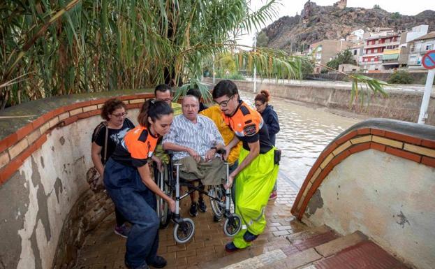 Voluntarios de protección civil trasladan a un hombre en silla de ruedas tras las intensas lluvias en Blanca (Murcia).