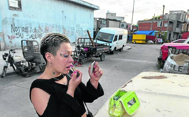 Una mujer se pinta en un barrio pobre de Buenos Aires.